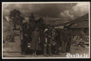 Kolchoznieki pēc kara Dunikā. Pie dzivojamās ēkas centrā sēž Līvija Role. Foto no Līvijas Roles.