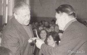 """Kolhoza """"Uzvara"""" pilnsapulce. Zigfrīdu Inni sveic priekšsēdētājs Žanis Stangevics."""