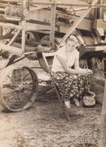 Ausma Kundziņa pie graudu vētāmās mašīnas.